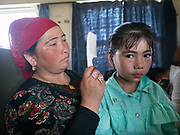 A mother brushes her daughter's hair. Life inside the train - mostly Muslim Uighur people  ride this train.