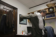 Alaska Representative Chris Tuck changes into his suit in his office at the state capital.
