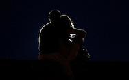 A couple embraces, silhouetted by a spotlight, at a prayer vigil ceremony for the 19 firefighters killed in the nearby Yarnell Hill wildfire in Prescott, Arizona July 2, 2013. REUTERS/Rick Wilking (UNITED STATES)