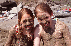 Brother and sister sitting on beach at seaside covered in sand laughing,
