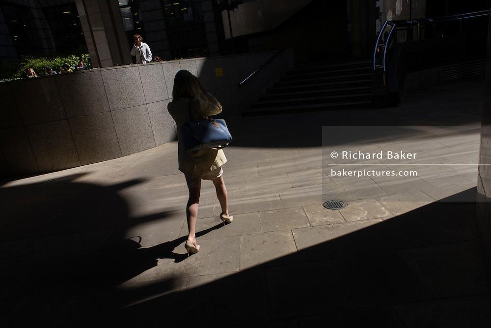 Woman walks through area of City of London sunlight.