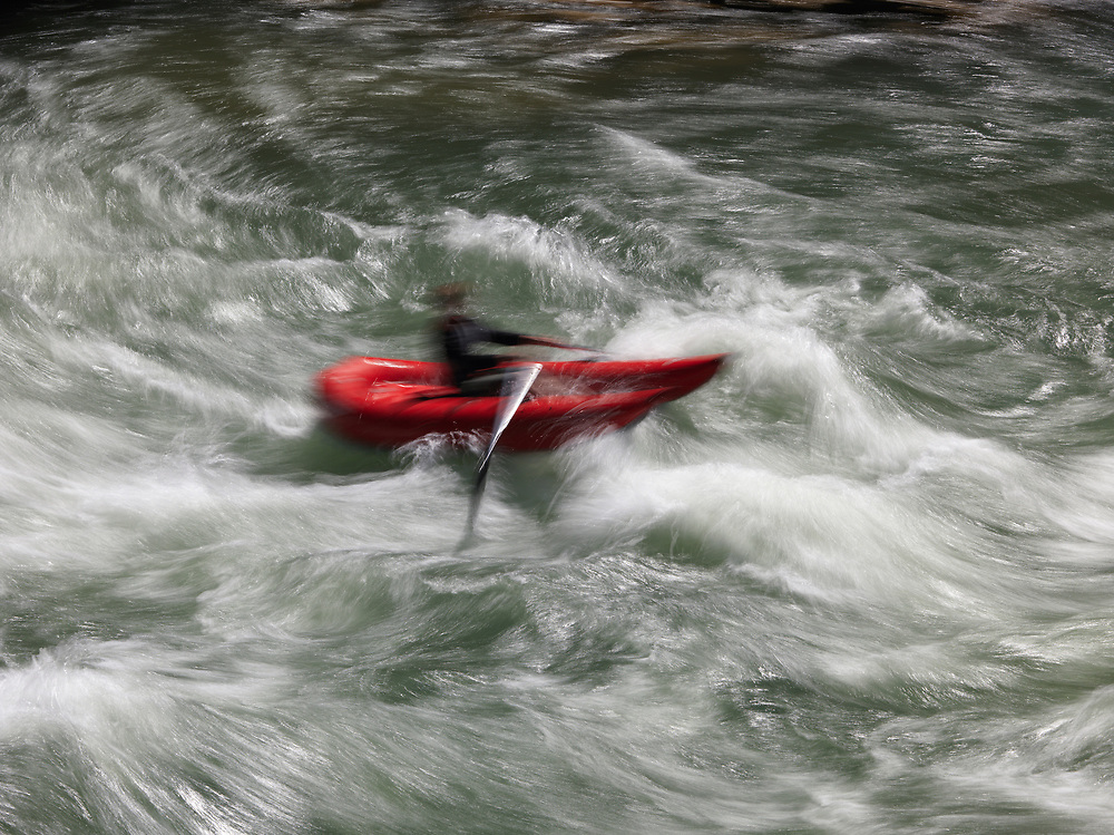 Rafting an inflatable kayak in blurred motion on the Big Kahuna Rapid on the Snake River near Hoback Junction in Wyoming.  Licensing and Open Edition Prints.