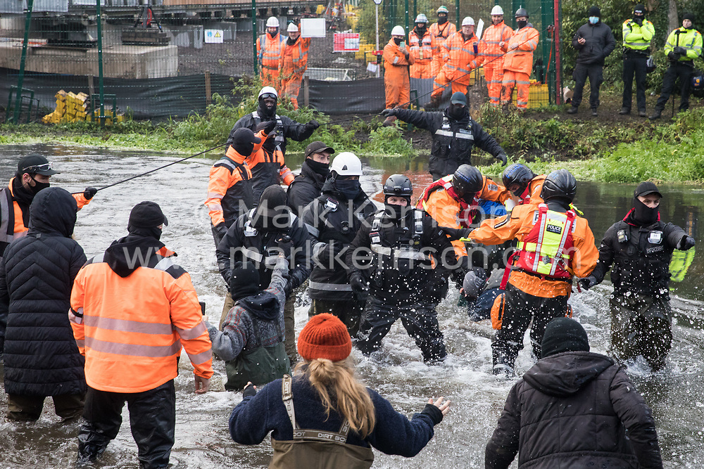 Denham, UK. 8th December, 2020. Hampshire Police officers remove an anti-HS2 activist from the river Colne for arrest whilst pushing another activist down towards the water during a large security operation to extract Dan Hooper, widely known as Swampy in the 1990s, from a bamboo tripod which he had occupied the previous day in order to delay the building of a bridge as part of works for the controversial HS2 high-speed rail link.