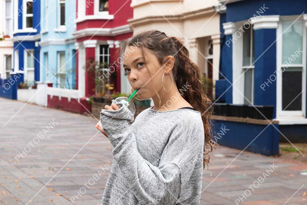 Portrait young girl with a smoothie in hand in a city context.