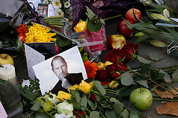 © Licensed to London News Pictures. 06/10/2011, London, UK. Apples, picture and flowers are seen left outside an Apple retail store in central London in tribute to Steve Jobs, Apple co-founder and former chief executive who died, age 56. Thursday, Oct. 6, 2011. Photo credit : Sang Tan/LNP