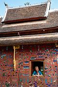 Image of a woman looking out a window at the Red Chapel, Wat Xiengthong, Luang Prabang, Laos.