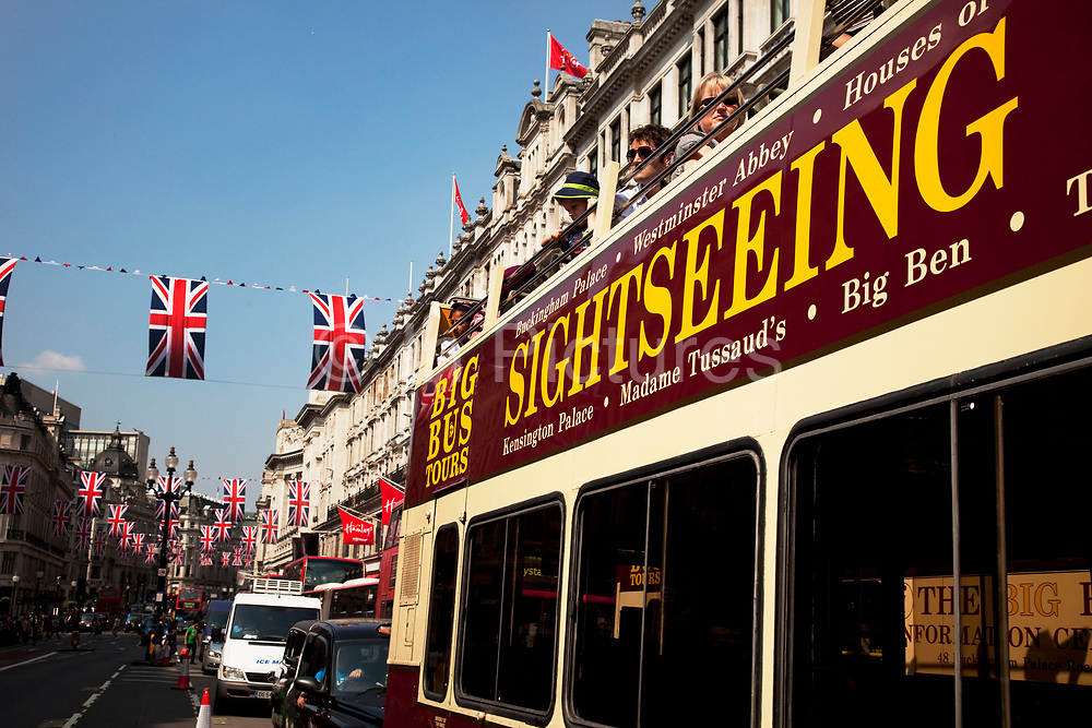 Sightseeing busses under Royal Wedding Union flags on Regent Street, London. A display of 200 giant Union Jack Flags run all the way along from Piccadilly Circus to beyond Oxford Circus. Each flag is 4 x 2.5 metres in size and hang from 22 crossings to celebrate the Royal Wedding, recreating a majestic architectural view of one of the world's most famous historical shopping thoroughfares.