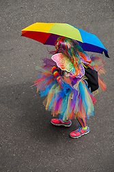 United States, Washington, Seattle. Seattle Gay Pride Parade, June 28th, 2015. Marcher with rainbow umbrella and clothing and butterfly wings.