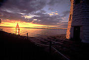 USA - Newport, RI - Shields yacht sails in front of sunset off the Green Light on Goat Isalnd in Narragansett bay.