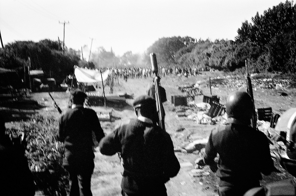 NAIROBI, KENYA - DECEMBER 31, 2007: Protesters attempt to charge through the last obstructing barricade between Kibera slum and Ngong Road. A shortage of rubber bullets was declared the reason why live ammunition was used to disperse demonstrators in Nairobi streets, but despite news briefings for non-aggressive police action, the rising death toll reflects questionable methods from the General Service Unit – a paramilitary wing of the Kenya police. The surge in violence left scores of people dead in Nairobi as defeated presidential candidate Raila Odinga prepared to declare himself head of state, after rejecting the victory of incumbent president Mwai Kibaki.