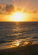 Chairs at waters edge at sunset on Saint Martin