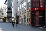 Two women wearing face masks walk down Oxford Street with all the shops closed, closed for business. March 24th 2020 was the first day of enforced lockdown in the UK, in order to stop the spread of the Coronavirus Covid 19. On what would normally be a bustling business / week day in London, the city was deserted, with just a few people in masks out on the street, plus a few taxis and mostly empty buses.