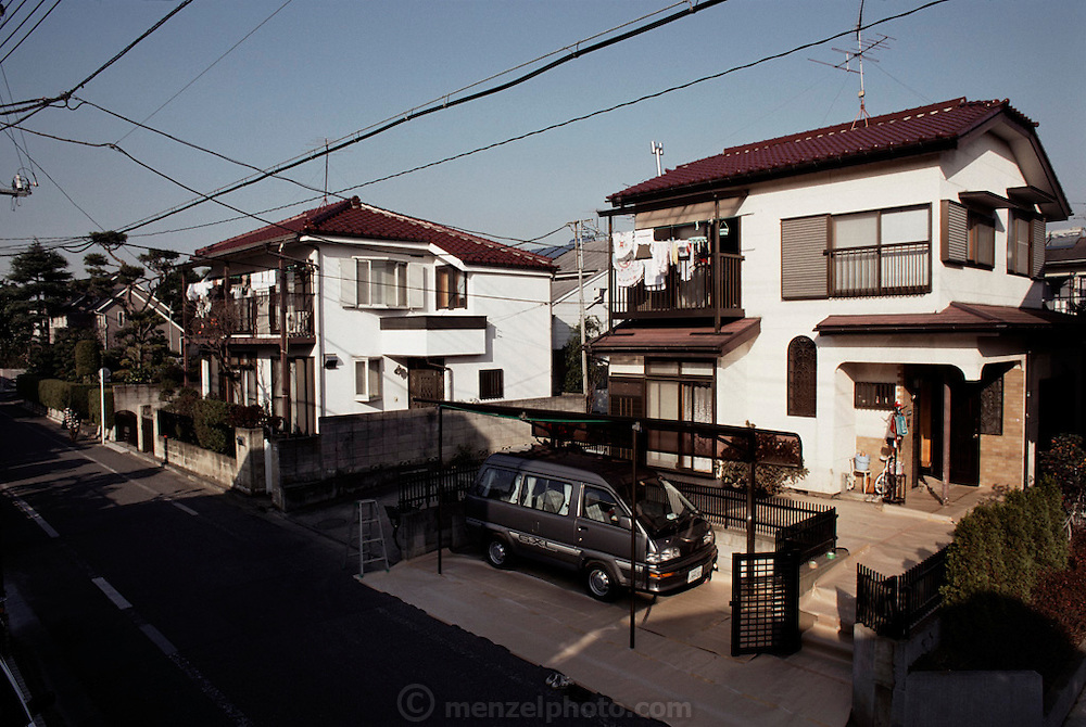 The Ukita family two story house with van under the carport. The Ukita family lives in a 1421 square foot wooden frame house in a suburb northwest of Tokyo, Japan, called Kodaira City. Material World Project.