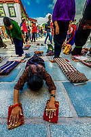 Tibetan pilgrims prostrating themselves outside the Jokhang Temple (most sacred temple in Tibet), Lhasa, Tibet (Xizang), China.