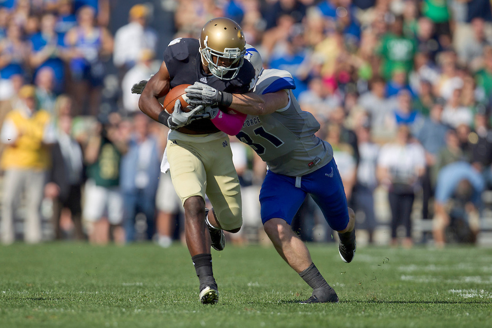 Notre Dame wide receiver Theo Riddick (#6) runs with the ball as Air Force defensive back Brian Lindsay (#31) defends in action during NCAA football game between Notre Dame and Air Force.  The Notre Dame Fighting Irish defeated the Air Force Falcons 59-33 in game at Notre Dame Stadium in South Bend, Indiana.