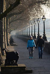 London, February 24th 2016. A couple walks along the River Thames at Cheyne Walk as the sun rises on a chilly but clear London morning. ///FOR LICENCING CONTACT: paul@pauldaveycreative.co.uk TEL:+44 (0) 7966 016 296 or +44 (0) 20 8969 6875. ©2015 Paul R Davey. All rights reserved.