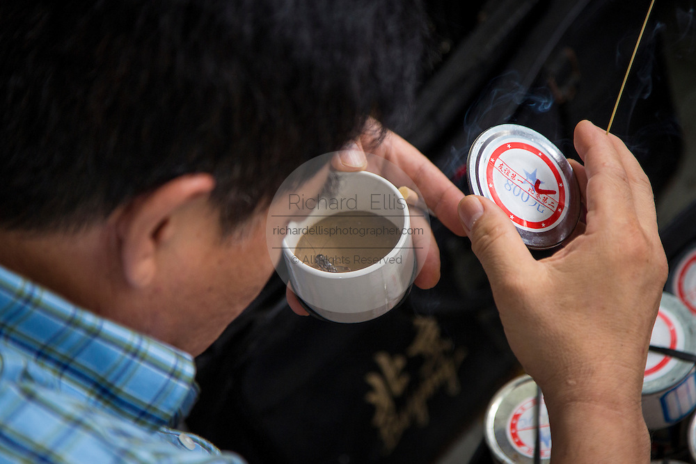 A man inspects fighting crickets at the Bird & Insect Market in Shanghai, China