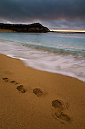 Waves breaking next to footprints in sand beach at sunset, Carmel River State Beach, California