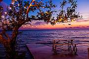 Table along the waterfront at sunset at Pineapples Bar on Green Turtle Cay, Bahamas.