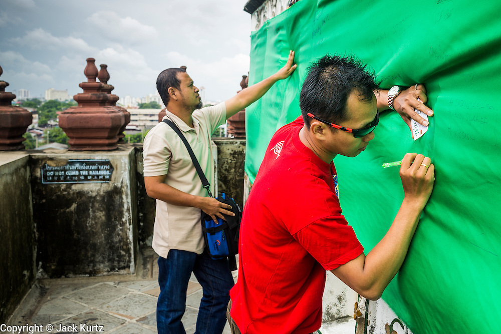 """23 SEPTEMBER 2013 - BANGKOK, THAILAND:  Tourists sign a sheet that covers the central prang at Wat Arun on the last day that tourists will be allowed to the top of the prang. The full name of the temple is Wat Arunratchawararam Ratchaworamahavihara. The outstanding feature of Wat Arun is its central prang (Khmer-style tower). The world-famous stupa, known locally as Phra Prang Wat Arun, will be closed for three years to undergo repairs and renovation along with other structures in the temple compound. This will be the biggest repair and renovation work on the stupa in the last 14 years. In the past, even while large-scale work was being done, the stupa used to remain open to tourists. It may be named """"Temple of the Dawn"""" because the first light of morning reflects off the surface of the temple with a pearly iridescence. The height is reported by different sources as between 66,80 meters and 86 meters. The corners are marked by 4 smaller satellite prangs. The temple was built in the days of Thailand's ancient capital of Ayutthaya and originally known as Wat Makok (The Olive Temple). King Rama IV gave the temple the present name Wat Arunratchawararam. Wat Arun officially ordained its first westerner, an American, in 2005. The central prang symbolizes Mount Meru of the Indian cosmology. The temple's distinctive silhouette is the logo of the Tourism Authority of Thailand.          PHOTO BY JACK KURTZ"""