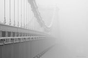 Thick morning fog envelops the Menai Suspension Bridge (Welsh: Pont Grog y Borth) which is a stone built Victorian suspension bridge between the island of Anglesey and Bangor and mainland of Wales. The 100ft high bridge was designed by Thomas Telford and completed in 1826.