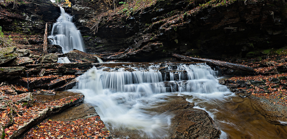 Ricketts Glen, Pennsylvania.<br /> <br /> Rain and overcast is a strong draw for Ricketts Glen.  It is a chance to shoot scenes like this, an overhanging grotto and fast flowing water that can't be captured with detail in a single shot on a bright day.  I would complete the loop trail up Ganoga Glen in darkness, losing the trail at the top and fumbling around awhile.  But here in Glen Leigh, the prettiest of the falls kept me awhile too long, lost in the ozone.<br /> Six vertical images were stitched in Photoshop to produce the panorama.