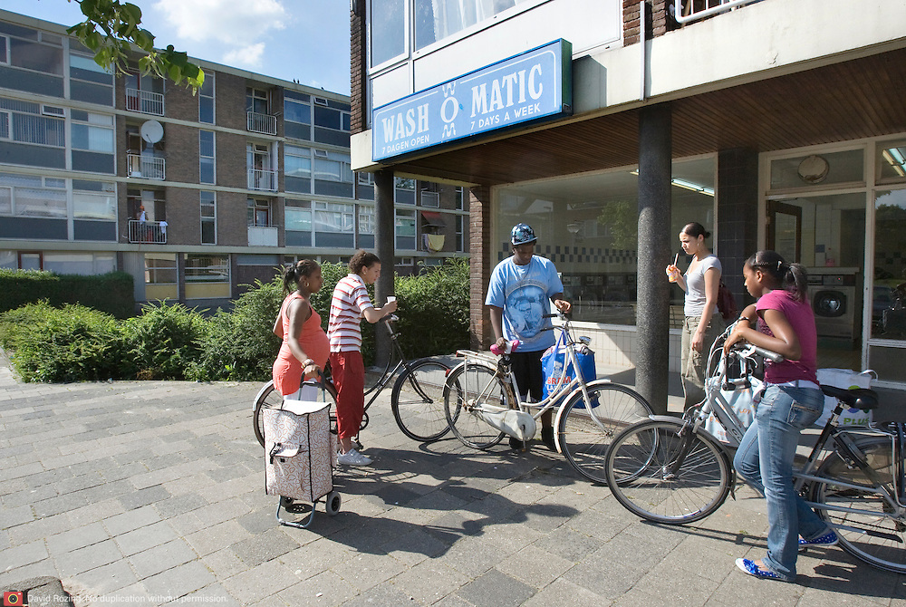 Nederland Rotterdam 01-06-2009 20090601 Foto: David Rozing   ..Achterstandswijk Pendrecht Rotterdam zuid. Jeugd voor wasserette, de was is zojuist gedaan en is in tassen gestopt om weer mee naar huis te nemen. Youth in deprived area / projects âEURoeKatendrecht âEURoe This area is on a list with projects which need help of the government because of degradation in the area etc., project, suburb, suburbian, problem. Neighboorhood, neighboorhoods, district, city, problems,  daily life Holland, The Netherlands, dutch, Pays Bas, Europe ..Foto: David Rozing/
