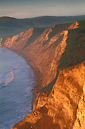 Golden sunrise light on steep coastal cliffs Drakes Bay Point Reyes National Seashore Marin California Sunrise light on coastal cliffs above Drakes Bay, Point Reyes National Seashore, Marin County, California