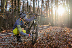 Mountain biker fixing front wheel of his bike on forest path, Bavaria, Germany