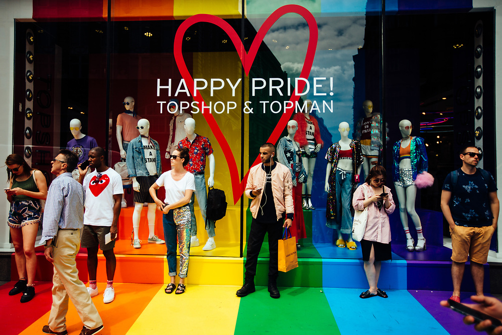 People are seen next to a shop window decorated with the Pride flag colors, during the Pride in London Parade, the Lesbian, Gay, Bisexual, and Transgender (LGBT) community parade in central London, England, on July 8, 2017. The annual event attracts hundreds of thousands of people who take to the streets in celebration and support of the LBGT+ community, making this the city's biggest one-day event and one of the world's biggest LGBT+ celebrations. This year's London Pride event marks 50 years since homosexuality was decriminalised in England and Wales under the 1967 Sexual Offences Act.