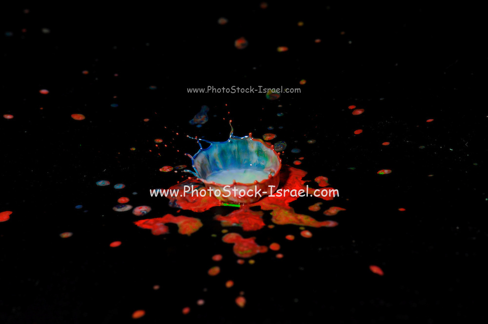 High-speed flash photograph milk droplets with colour dye. The droplet lands in the liquid and produces a coronet.