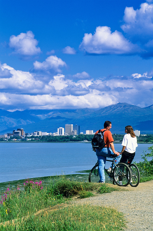 Alaska. Anchorgae. Tony Knowles Coastal Trail. a couple enjoys the sunshine along Cook Inlet with Anchorage in distance. Chugach Mountains.