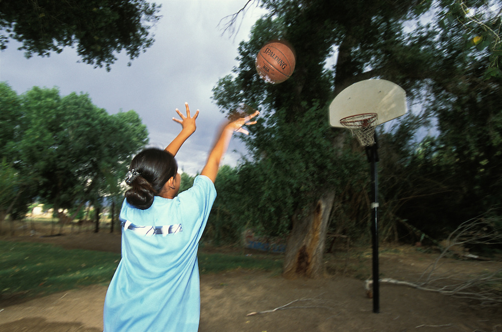 An Apache girl plays basketball in the back yard of her home in Bylas, on the San Carlos Apache Indian Reservation in Arizona, USA. June 2004.