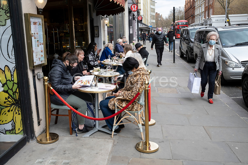 People eating at a restaurant with tables on the pavement as an elderly lady on the Kings Road in the upmarket area of Chelsea on 14th April 2021 in London, United Kingdom. Chelsea is one of the principal areas for exclusive, luxury goods in West London. It is known as a district where the rich and wealthy shop, mostly for high street and high end fashion and jewellery.