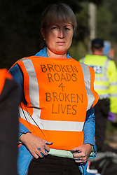 Ockham, UK. 21st September, 2021. An Insulate Britain climate activist waits, under arrest by Surrey Police, on the hard shoulder of the M25 after blocking the clockwise carriageway between Junctions 9 and 10. Activists briefly halted traffic on both carriageways of the motorway as part of a campaign intended to push the UK government to make significant legislative change to start lowering emissions.