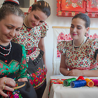 Girls watch as a woman sews traditional Matyo embrodiery in Mezokovesd, Hungary on April 5, 2012. ATTILA VOLGYI