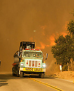 A fire engine passes by the wildfire near Placenta Caynon Road in Santa Clarita, Calif., Sunday, July 24, 2016.(AP Photo/Ringo H.W. Chiu)
