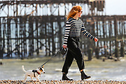 April 6, 2020, London, England, United Kingdom: A girl walks her dog on the beach in Brighton, Britain on Monday, April 6, 2020 - as British Prime Minister Boris Johnson was moved to intensive care after his coronavirus symptoms worsened in London. Johnson was admitted to St Thomas' hospital in central London on Sunday after his coronavirus symptoms persisted for 10 days. Having been in hospital for tests and observation, his doctors advised that he be admitted to intensive care on Monday evening. The new coronavirus causes mild or moderate symptoms for most people, but for some, especially older adults and people with existing health problems, it can cause more severe illness or death. (Credit Image: © Vedat Xhymshiti/ZUMA Wire)