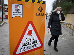 © Licensed to London News Pictures. 01/02/2021. Woking, UK. A members of the public wearing a face mask walks past a Coronavirus alert sign in Woking town centre in Surrey, where a South African variant of Covid-19 has been found. Photo credit: Ben Cawthra/LNP