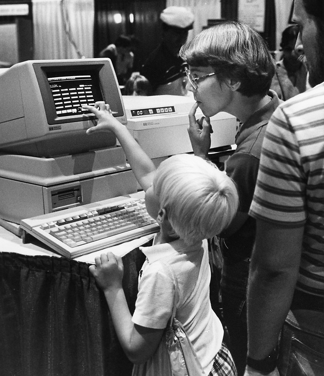 ©1986 mother and child at a computer display at a convention, Austin, TX