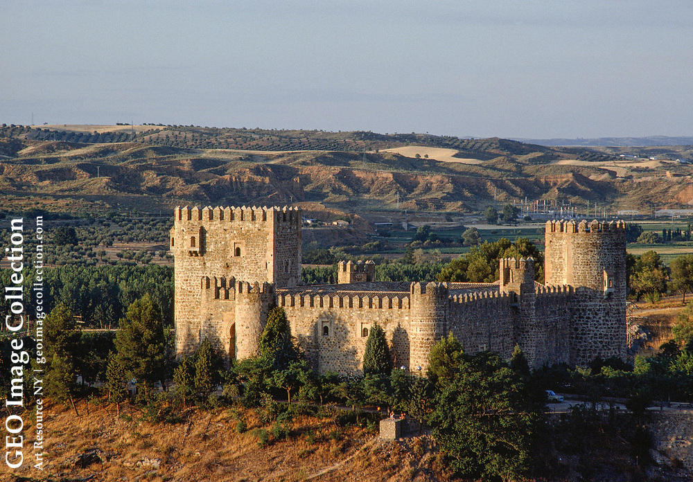 The late-14th-century castle of San Servando sits on a hillside in evening ligh t, an old crenellated Moorish fortress, located just across the River Tagus (Ri o Tajo) from Toledo.  It was taken over by Christians after Alfonso VI conquere d the city in A.D. 1085.