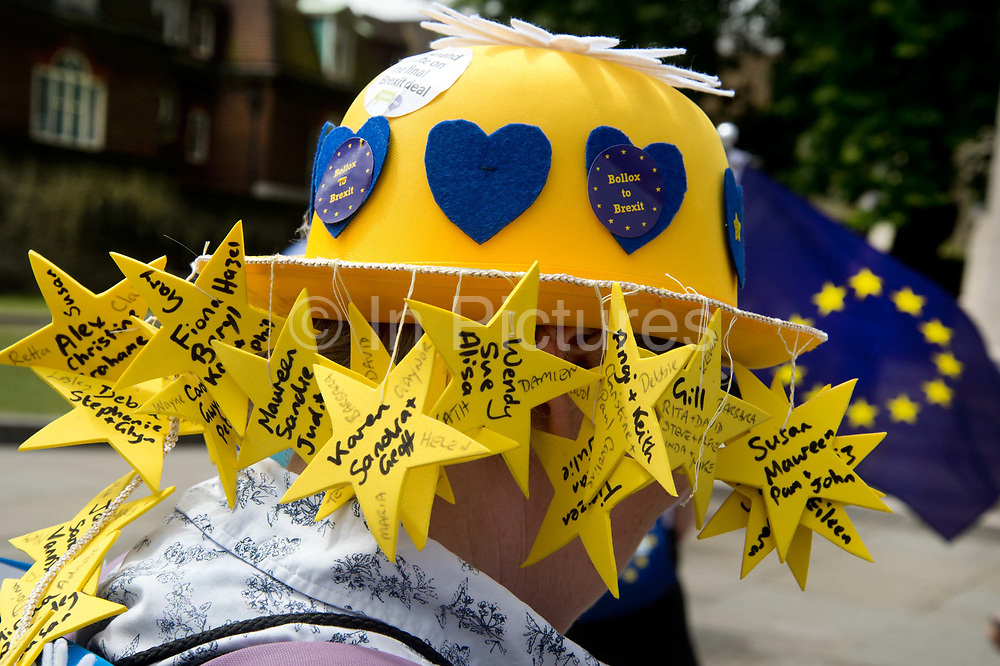 Anti Brexit protesters outside Parliament, Westminster, London as Members of Parliament debate the European Union withdrawal bill, June 20th 2018. A woman from Poole, Dorset wears a hat with the names of British ex patriates living in Spain who were not able to return to Britain to vote in the EU referendum.