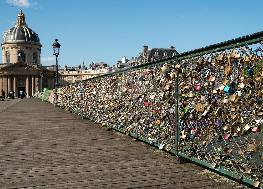 Couples leave locks on a bridge over the Seine River.