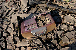 30 Sept, 2005. New Orleans, Louisiana. Lower 9th ward. Hurricane Katrina aftermath. <br /> The remnants of the lives of ordinary folks, now covered in mud as the flood waters remain. A CD radio player lies covered in mud.<br /> Photo; ©Charlie Varley/varleypix.com
