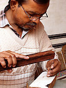 A master carver traces the design for a woodblock with a small chisel. Anokhi Museum of Hand Printing, Amber, Rajasthan