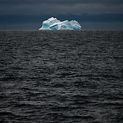 A large blue iceberg floats on the horizon against dark seas and skies in the northern Antarctic Peninsula.