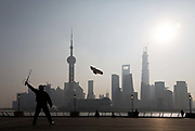 A man flies his kite on the Bund with Pudong in the distance as the backdrop in Shanghai, China on 13 October 2013. The Bund, along with the contrast of the modern skyline across the Huangpu River in Pudong's Lujiazui Financial District, is one of the most iconic tourist destination in China and possibly the world.