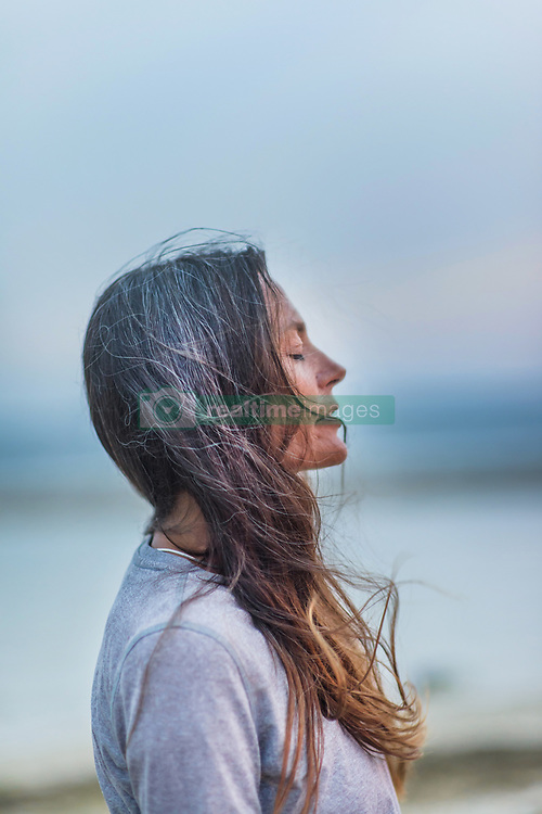 July 3, 2016 - Profile of mature woman outdoors, eyes closed, wind blowing hair (Credit Image: © Sue Barr/Image Source via ZUMA Press)