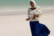A schoolgirl walking along Kiwendwa Beach  wearing a white headscarf and blue skirt.  Zanzibar, Tanzania