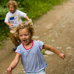 Young kids (age 4) run on a woodland trail in Turner, Maine. (MR)